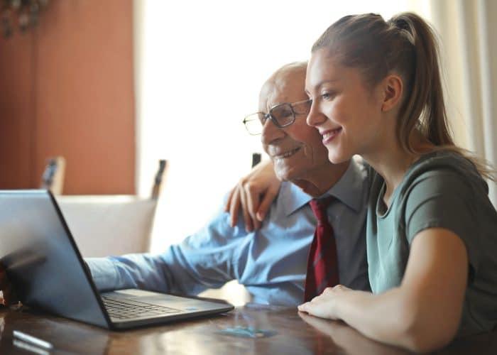 Grootvader en kleinkind kijken naar laptop
